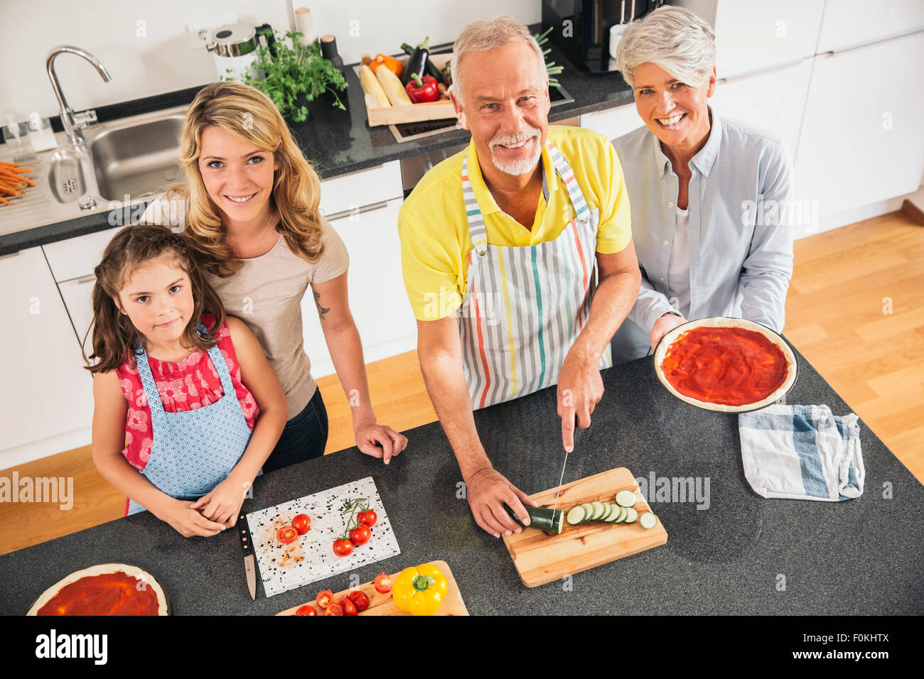 Group picture of three generations family in the kitchen - Stock Image