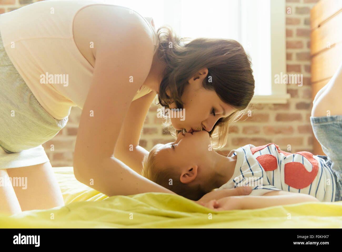 Pregnant mother kissing her son lying on bed at home - Stock Image