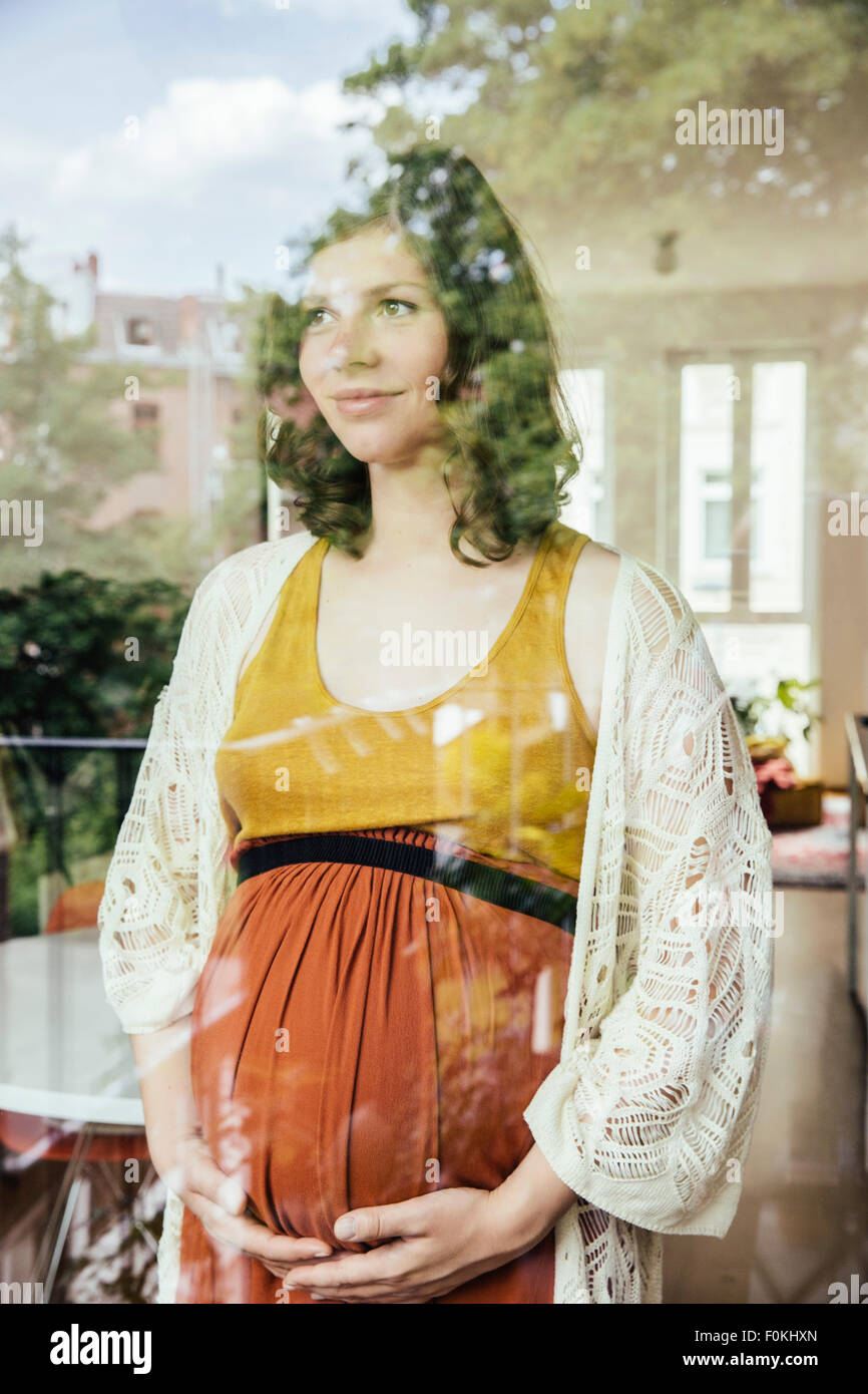 Portrait of pregnant woman looking through the window - Stock Image