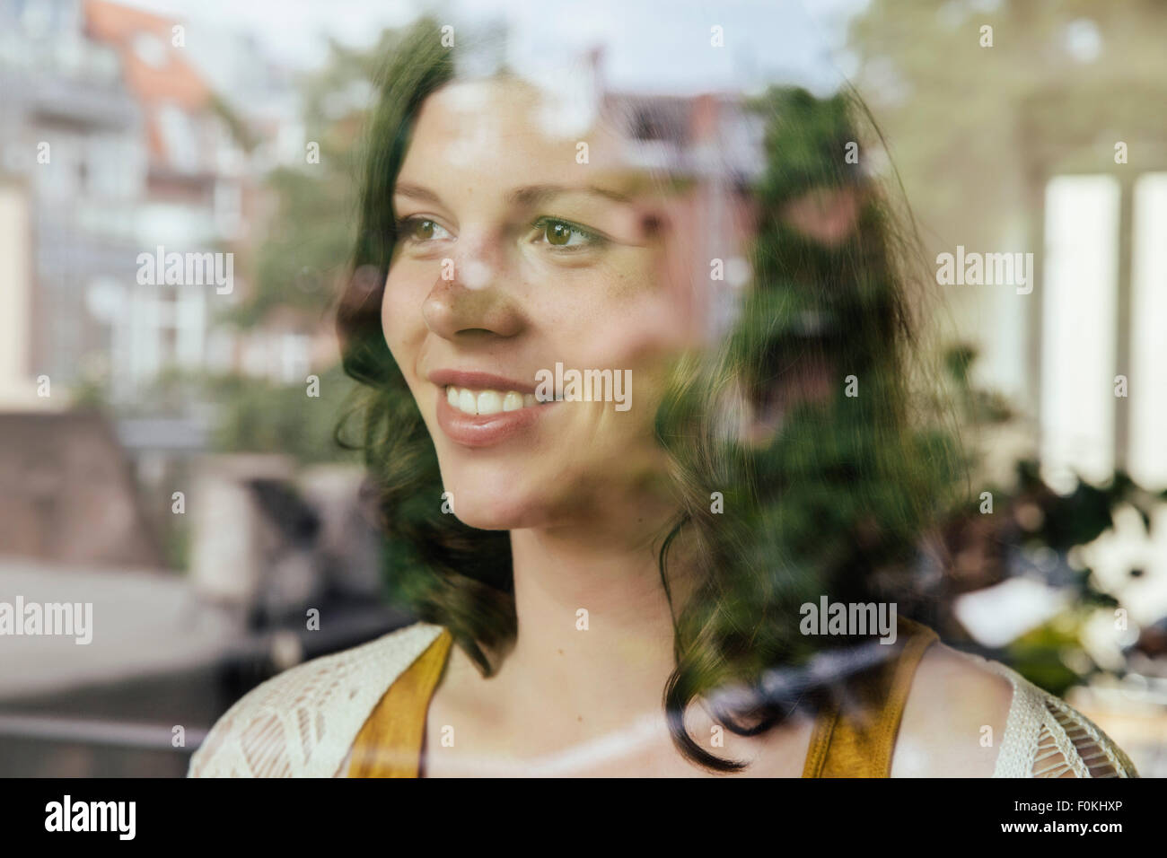 Portrait of woman looking through the window - Stock Image