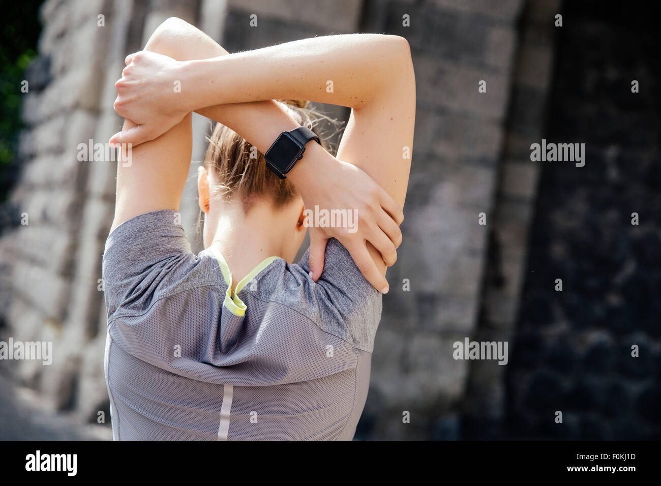 Young sporty woman with smart watch stretching - Stock Image