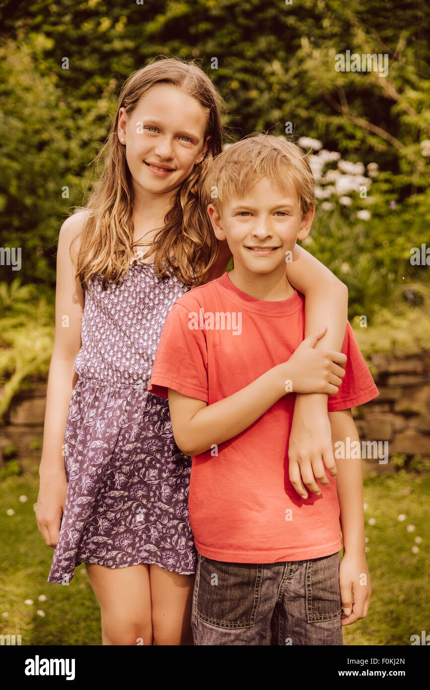 Smiling girl putting arm around brother in garden - Stock Image