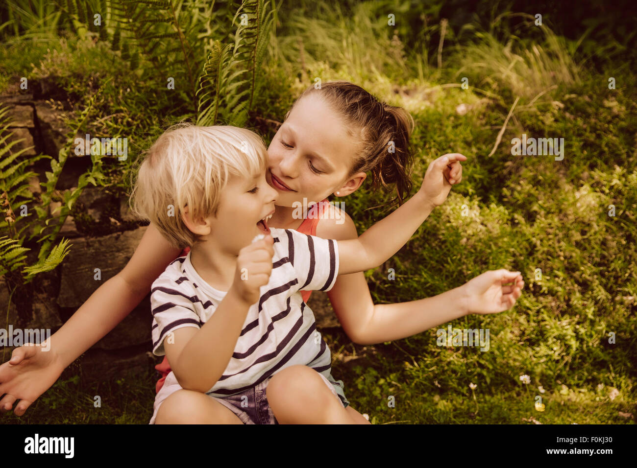 Girl and little boy playing in garden Stock Photo