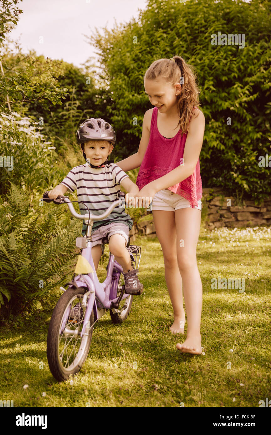 Girl helping little boy riding bicycle in garden Stock Photo ...