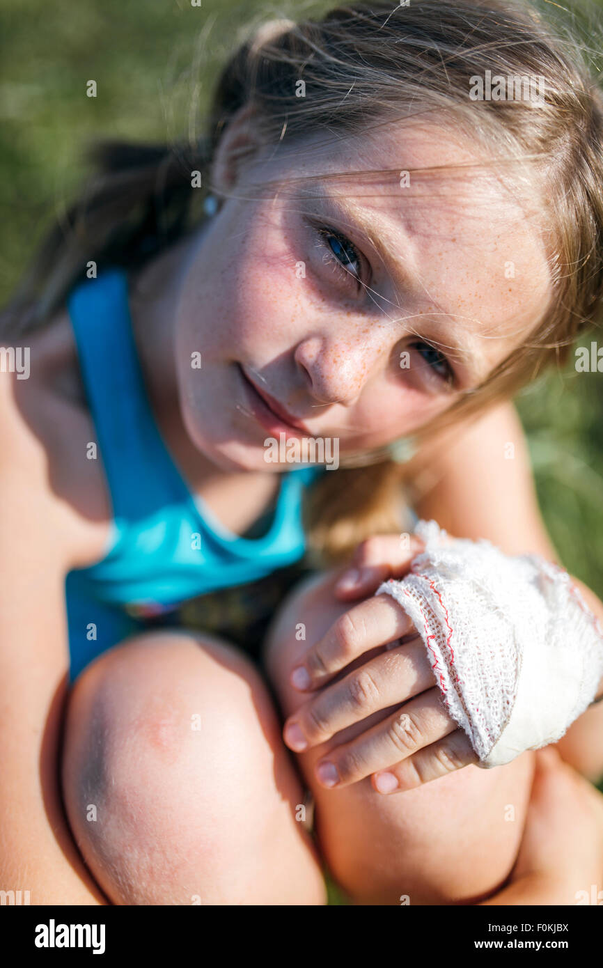 Portrait of blond girl with gauze bandage on her hand - Stock Image