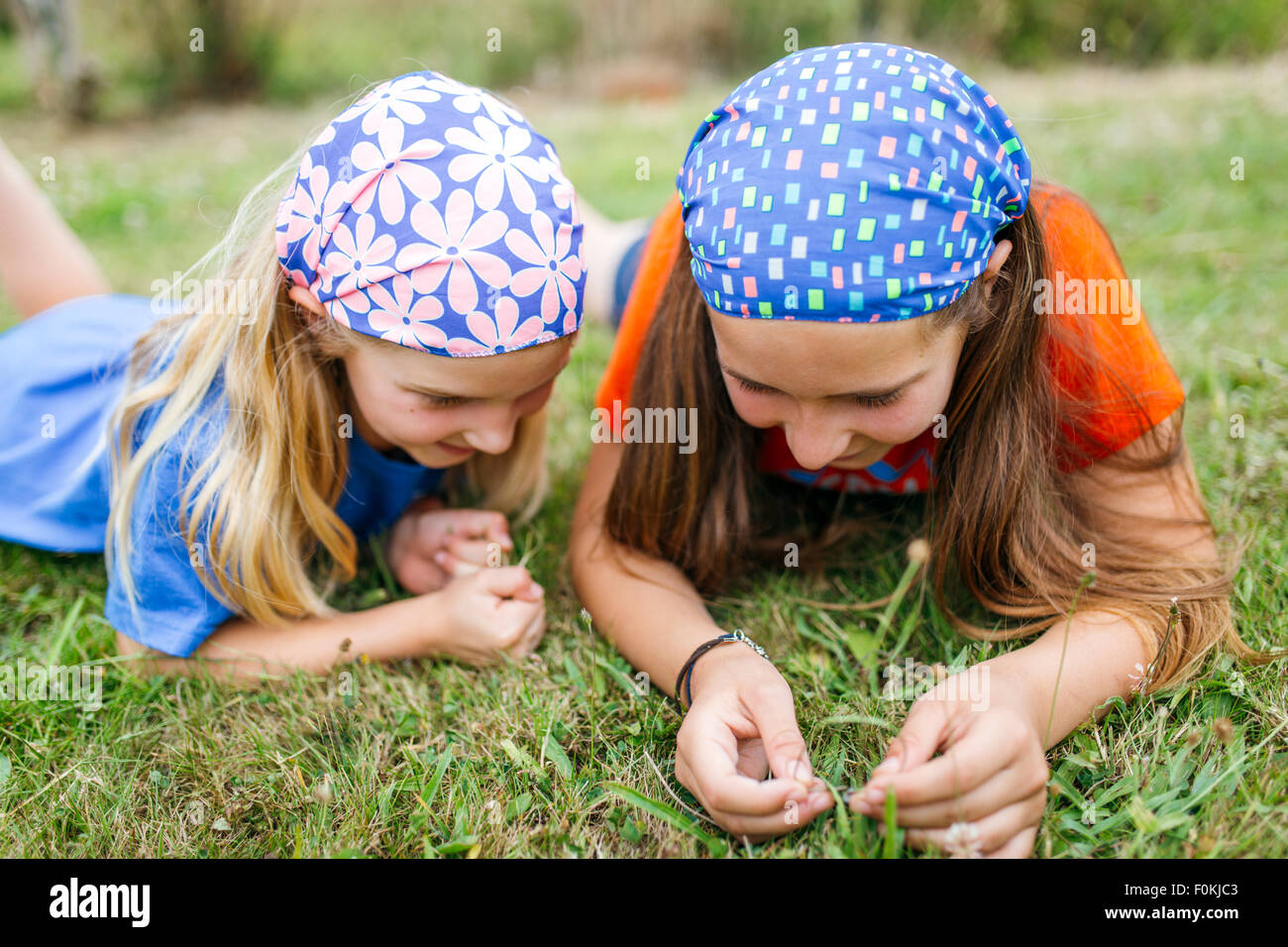 Two little sisters lying on a meadow - Stock Image