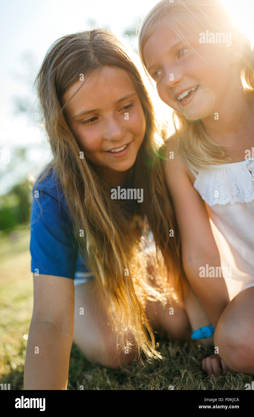 Two sisters crouching side by side on a meadow - Stock Image