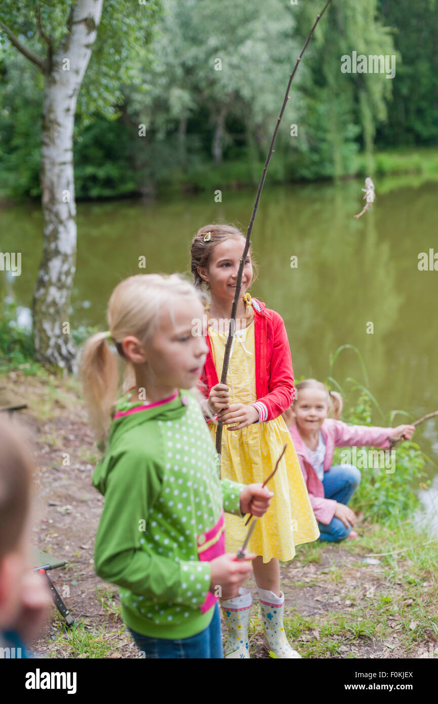 Germany, Girls with rods and small fish - Stock Image