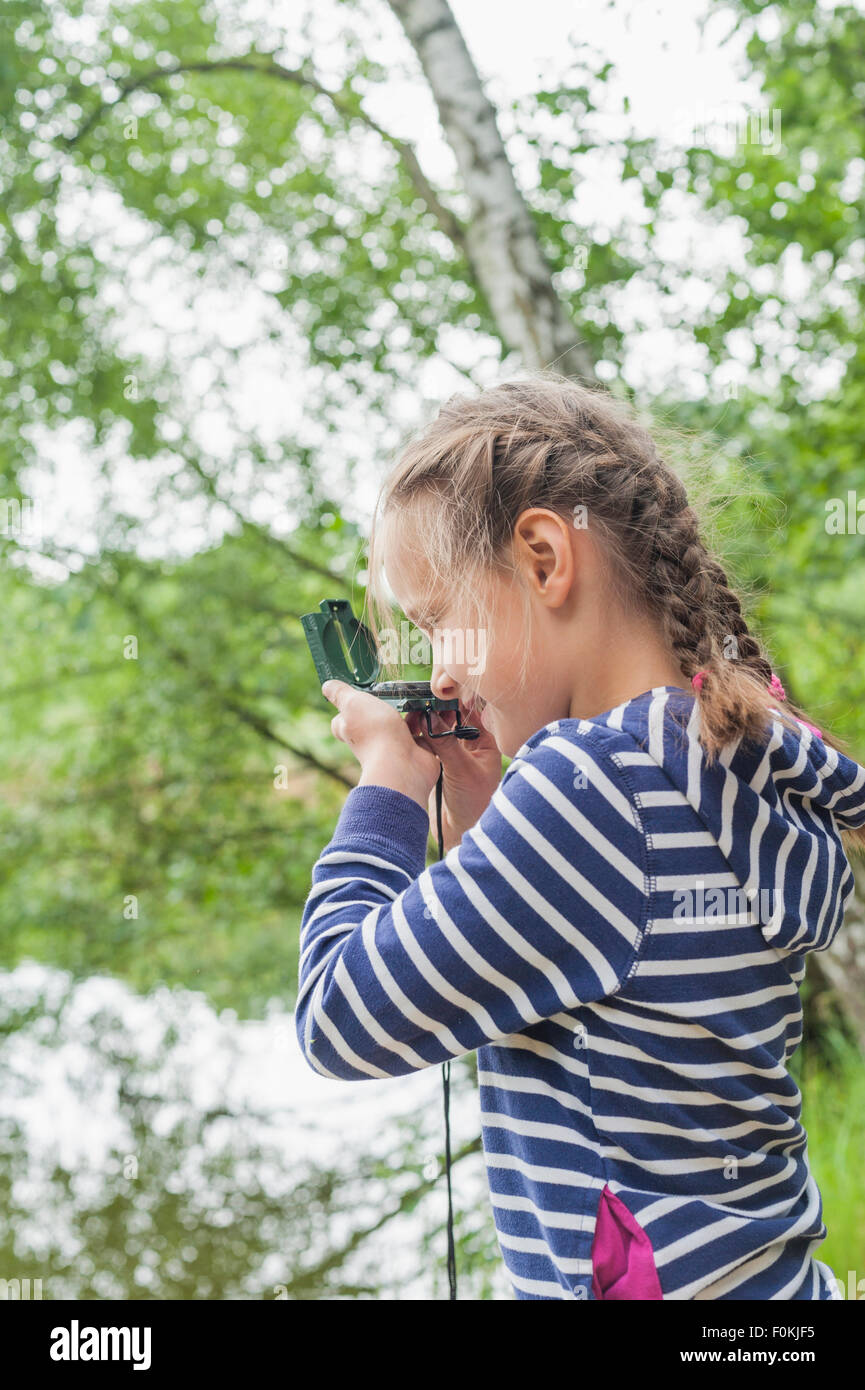 Germany, Girl looking through compass - Stock Image