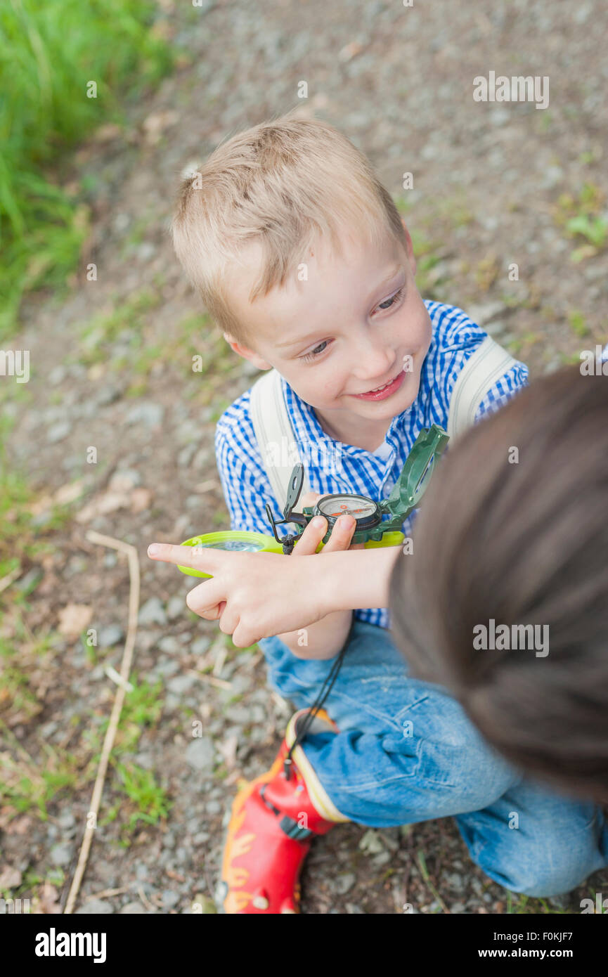 Germany, Boy learning how to use compass - Stock Image