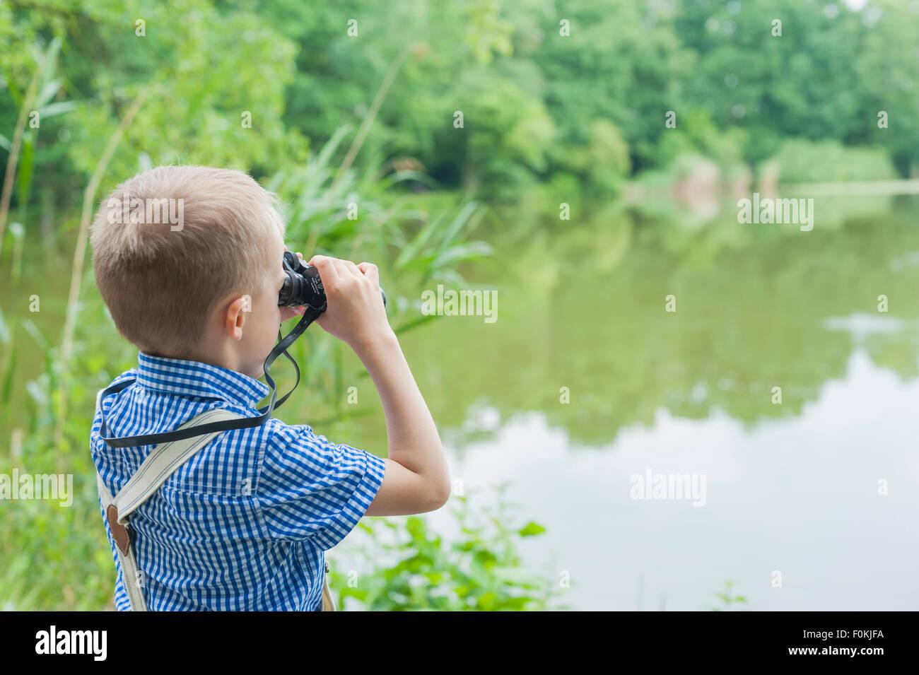 Germany, Boy with binoculars watching animals - Stock Image