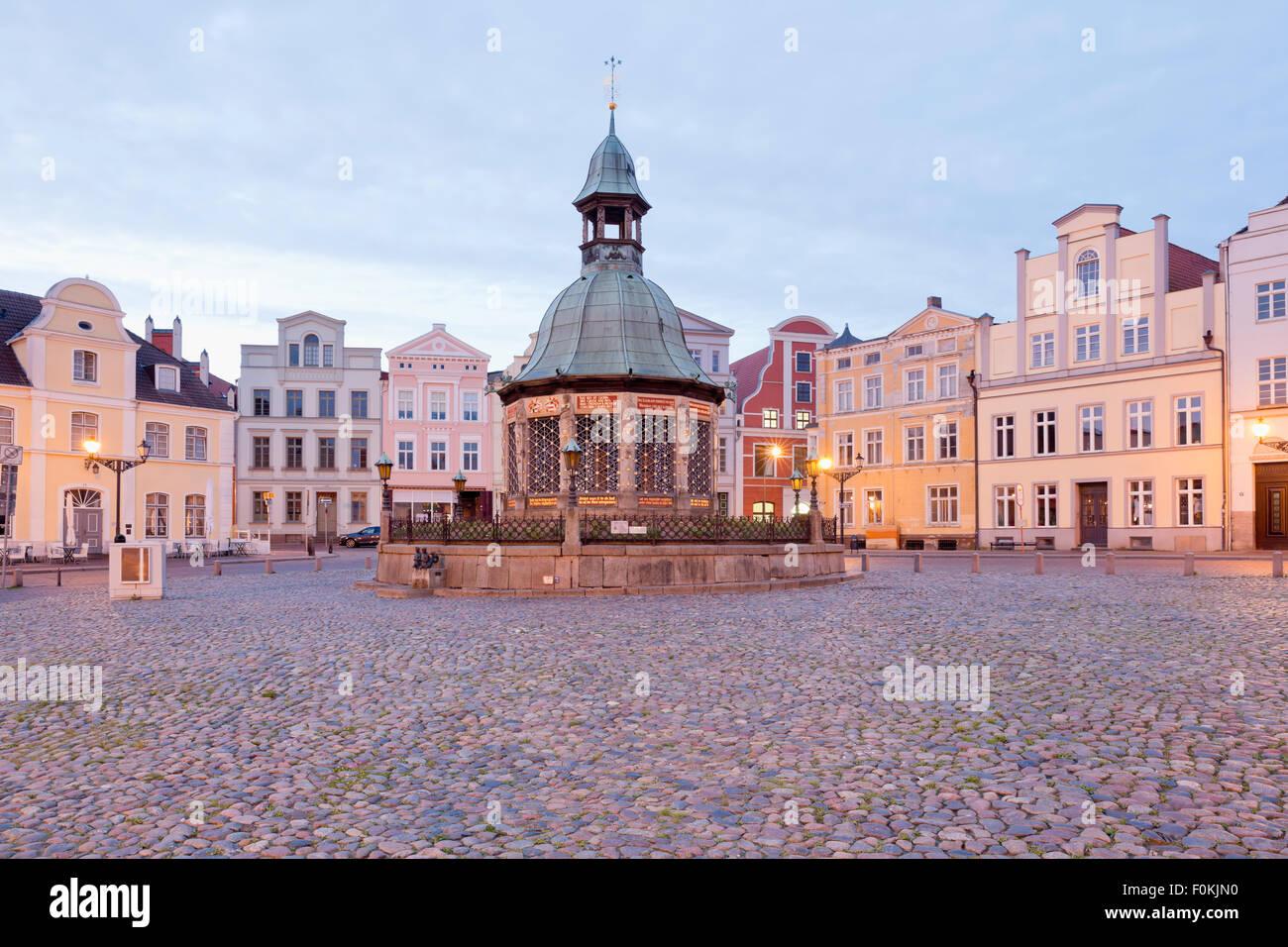 Germany, Wismar, market square with Wasserkunst at twilight - Stock Image