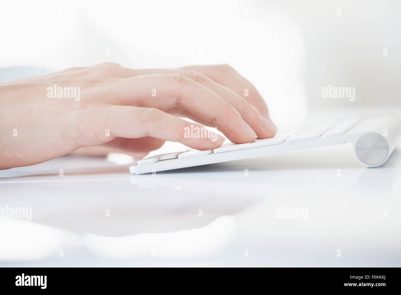 Close-up of woman's hand typing on keyboard - Stock Image