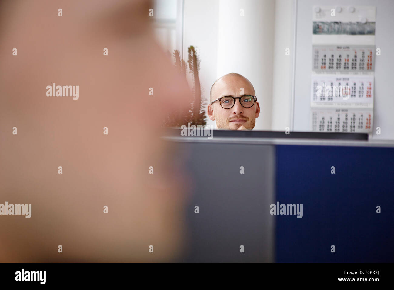 Confident man in office behind computer screens - Stock Image