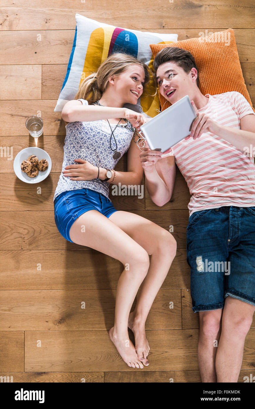 Happy young couple lying on floor sharing digital tablet - Stock Image