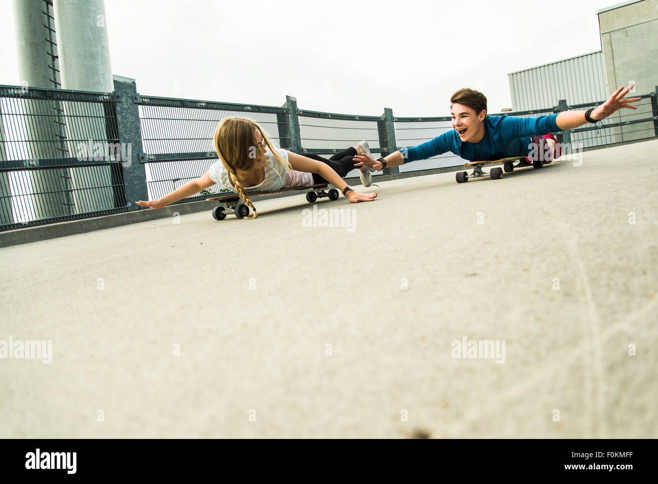 Enthusiastic young couple riding downhill with skateboards - Stock Image