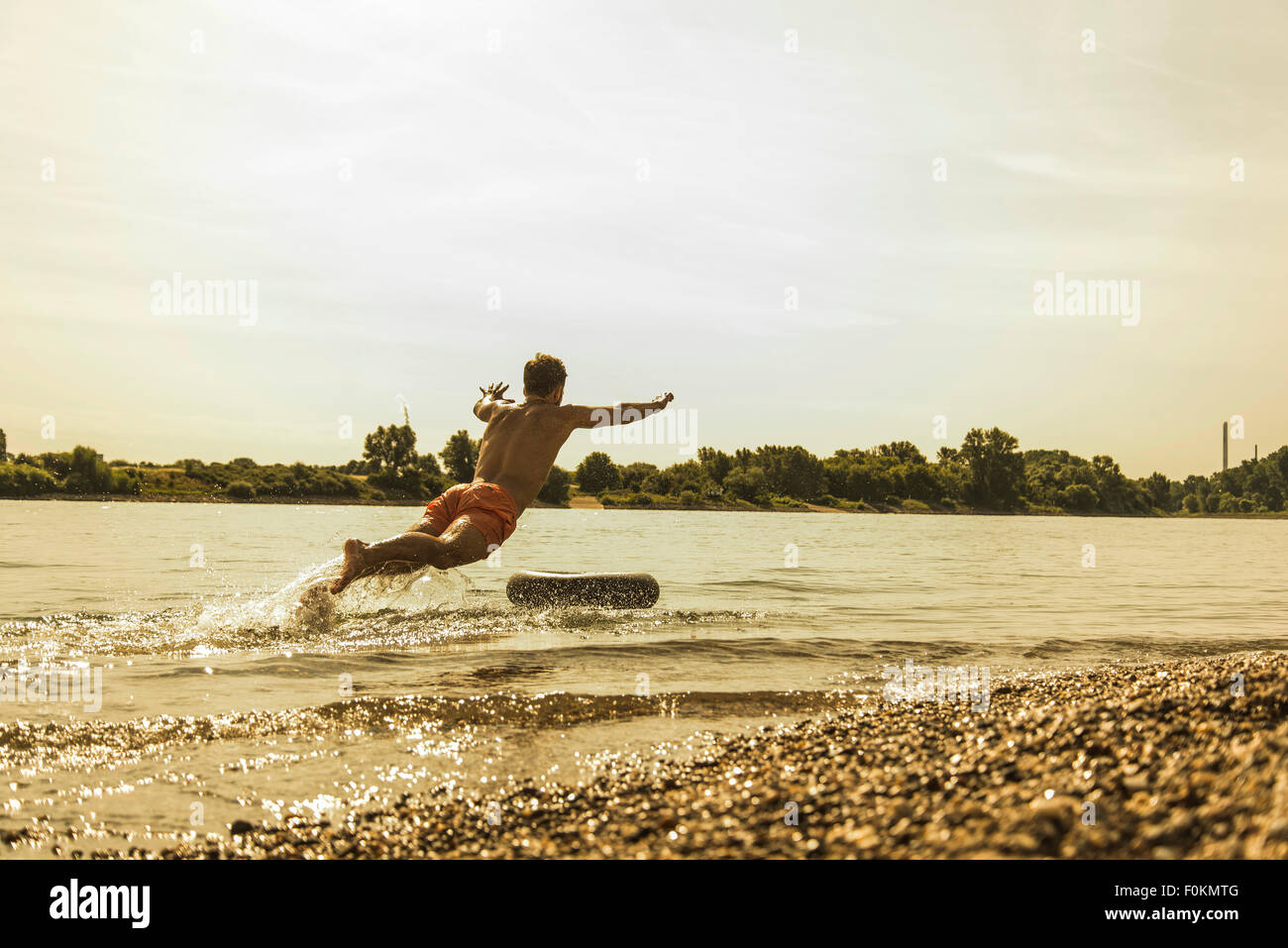 Young man jumping in river with inner tube - Stock Image