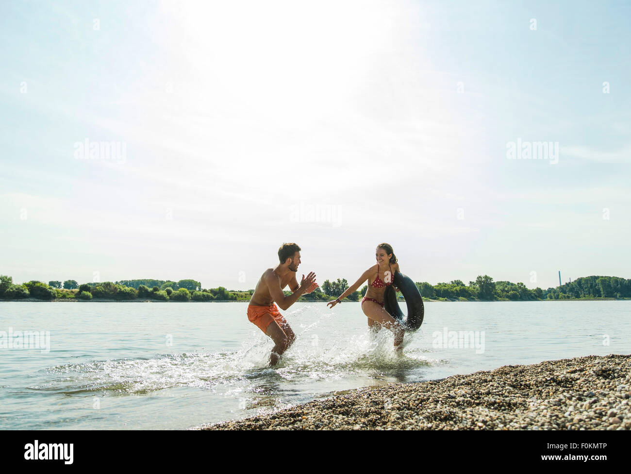 Playful young couple with inner tube in river - Stock Image