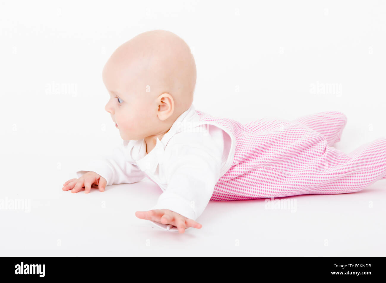 actively crawling wearing a romper baby. studio photo - Stock Image