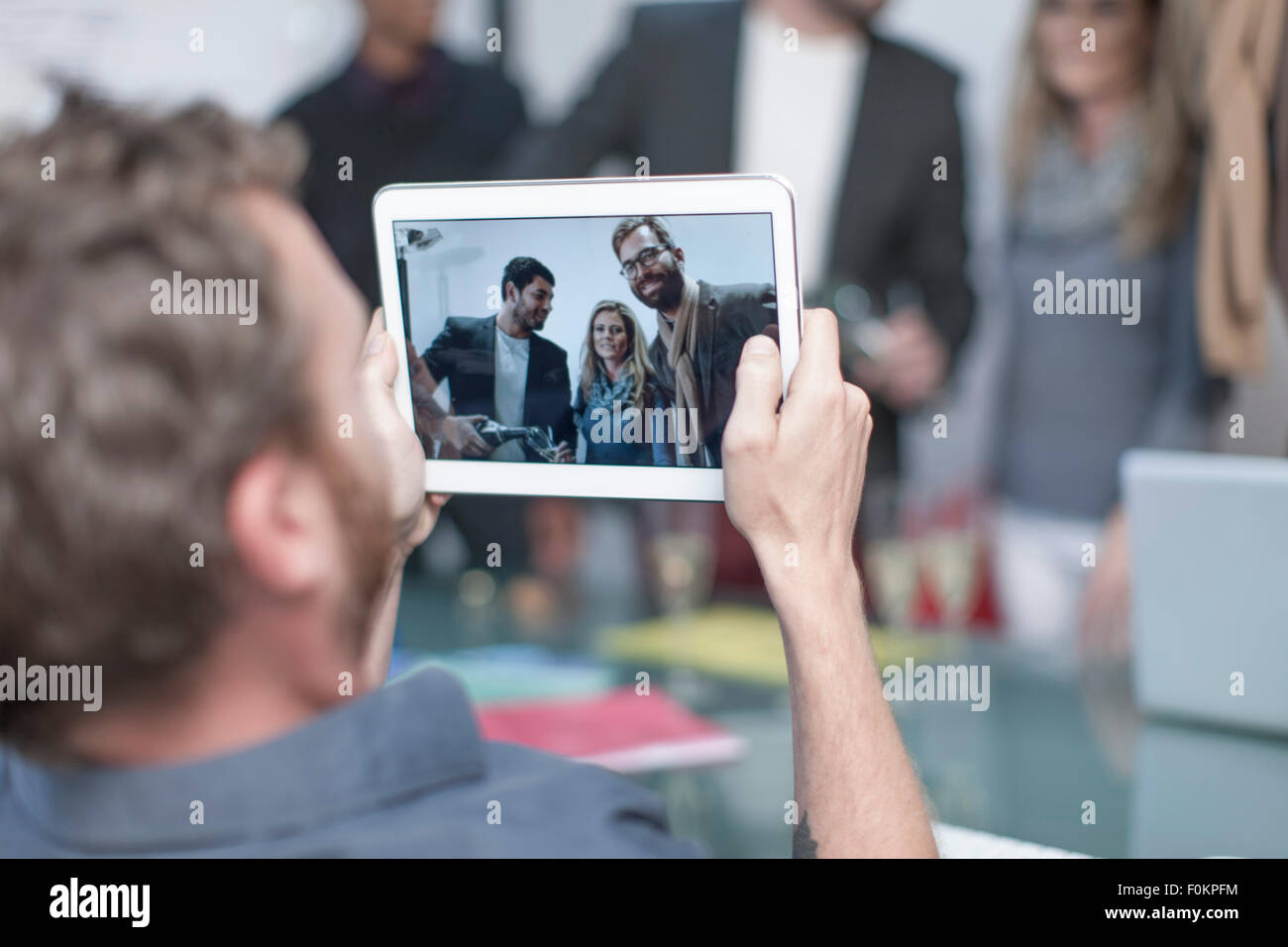 Man taking a photo of colleagues on a digital tablet - Stock Image
