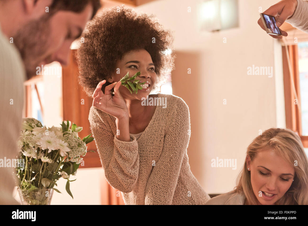 Young woman posing with leaf from bunch of flowers for a photo - Stock Image