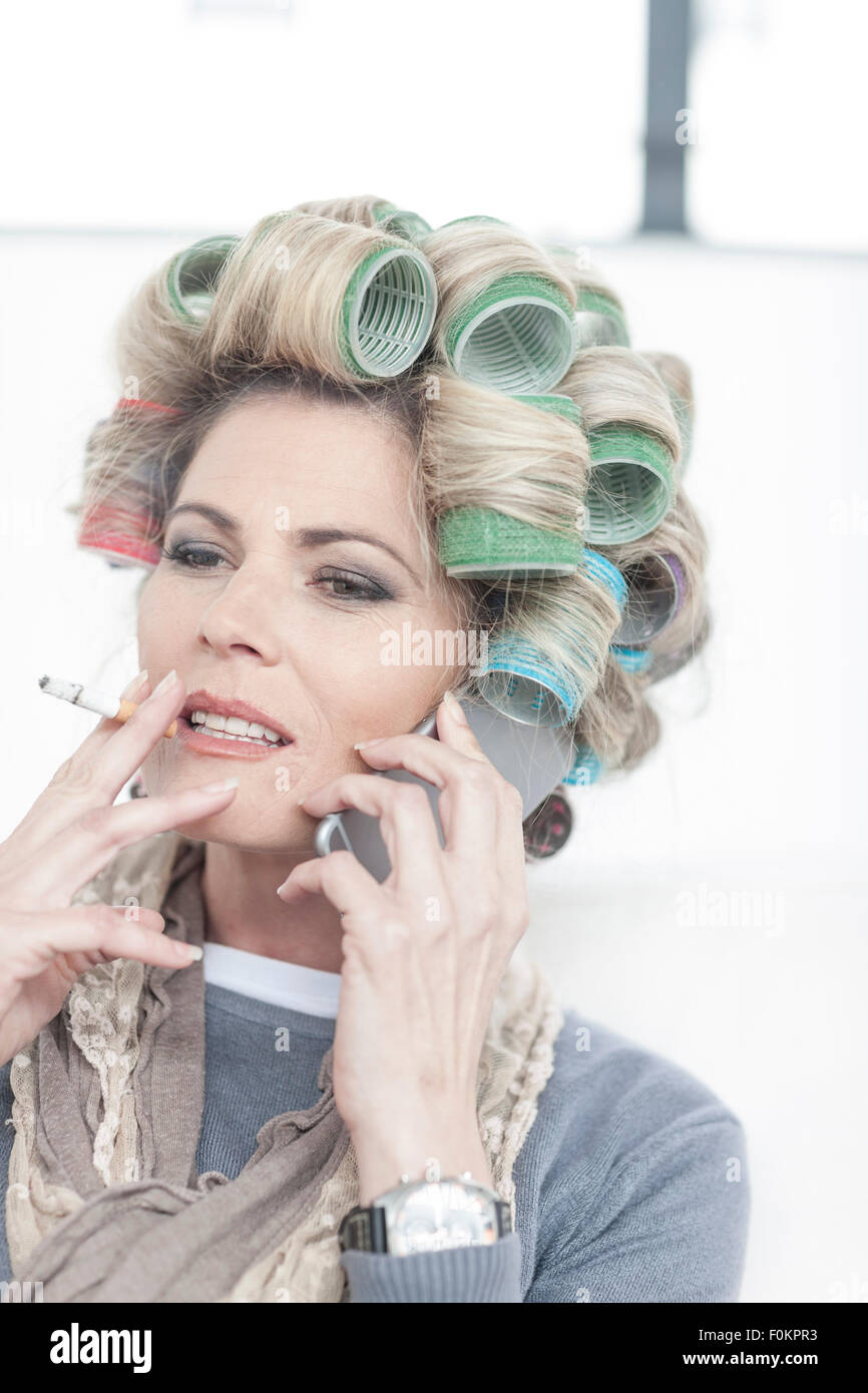 Portrait of woman with hair curlers smoking a cigarette ...