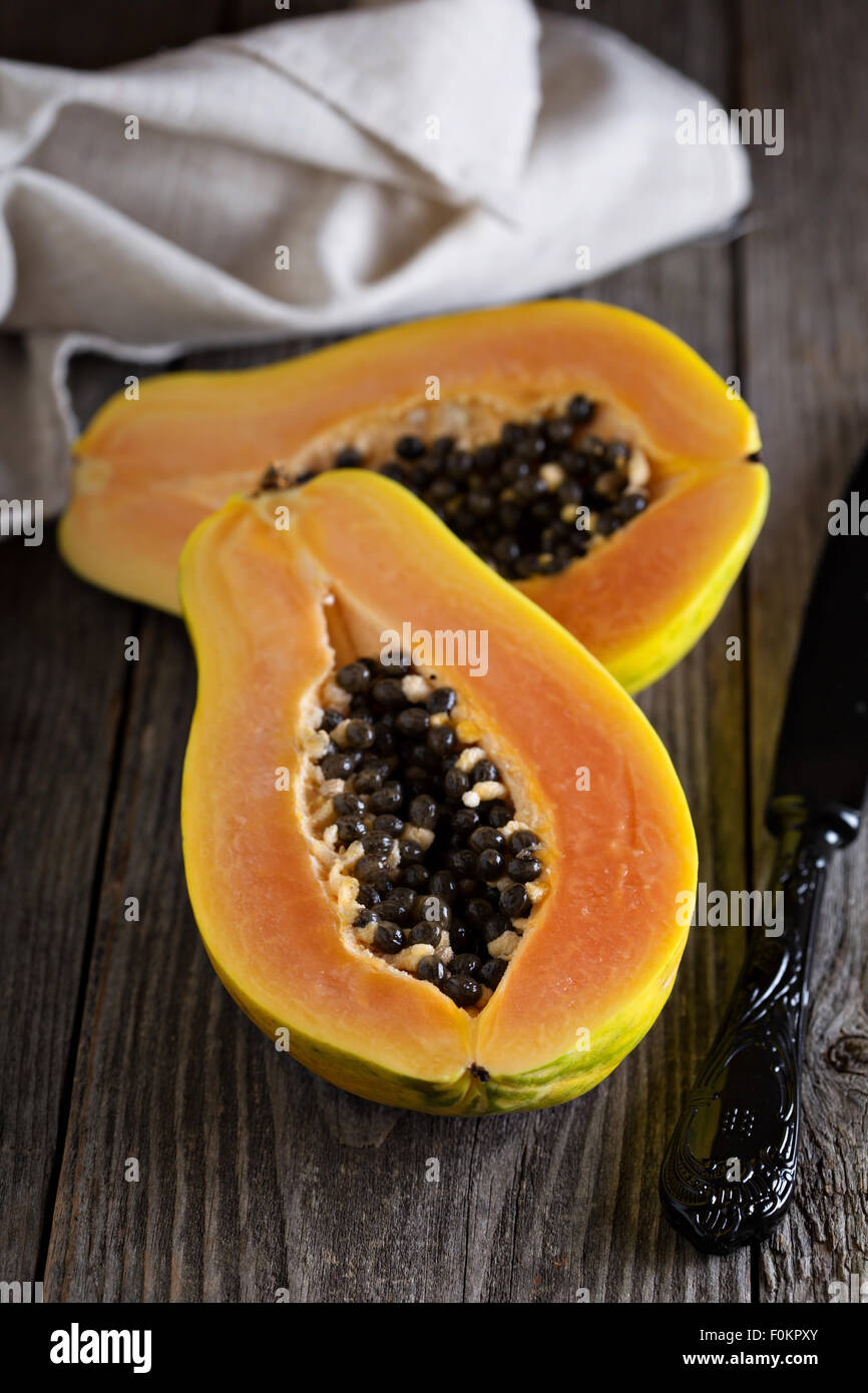 Cut papaya exotic fruit on a wooden table - Stock Image