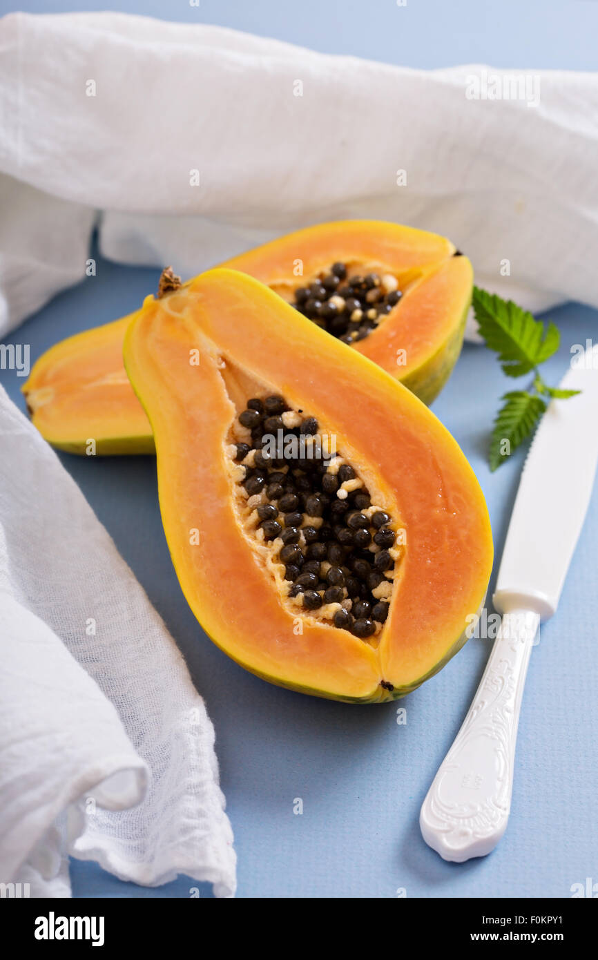 Cut papaya exotic fruit on a blue table - Stock Image
