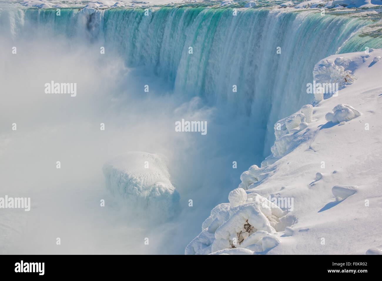 A partially frozen Horseshoe Falls deposits 600,000 gallons a second into the Niagara River in Niagara Falls, Canada. - Stock Image
