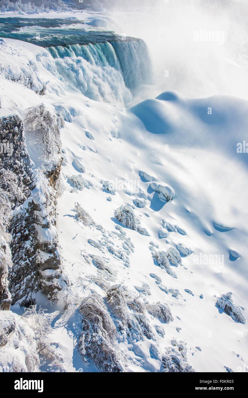 A partially frozen Horseshoe Falls deposits 600,000 gallons a second into the Niagara River in Niagara Falls, New - Stock Image