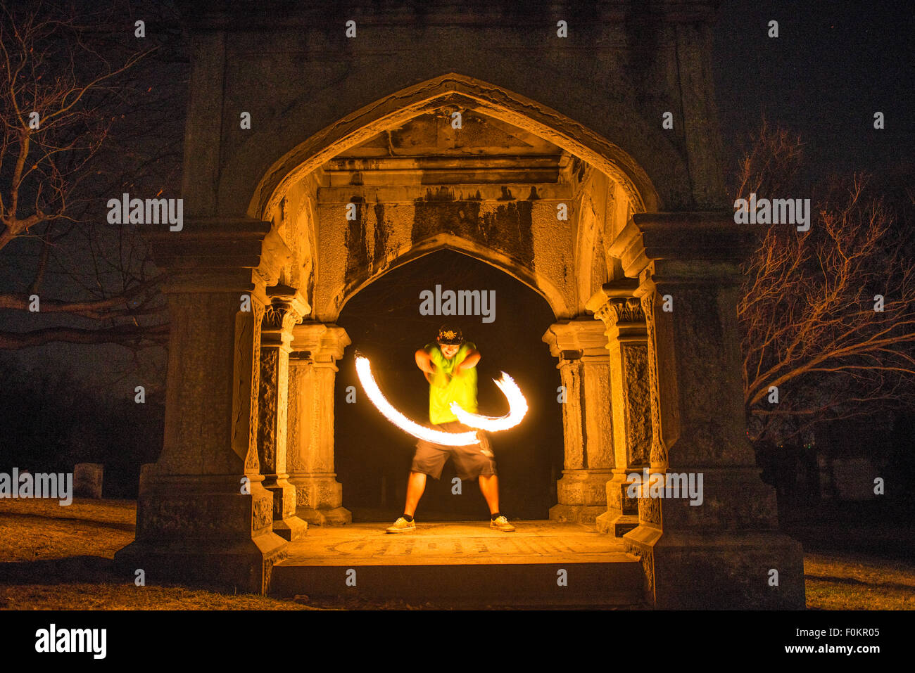 A college student spins and juggles fire in Oakwood Cemetery in Syracuse, New York. - Stock Image
