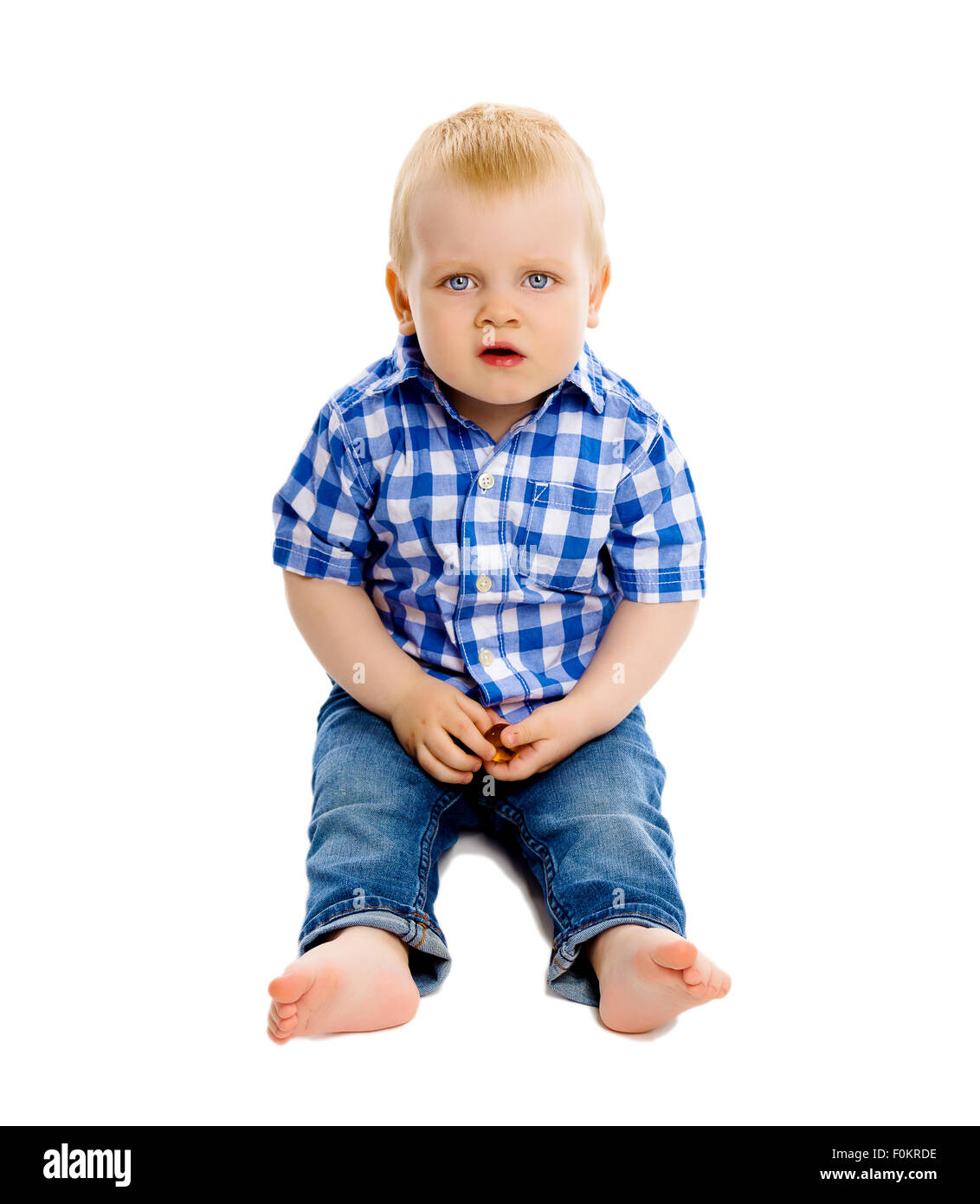 Little dissatisfied boy in a plaid shirt and jeans on white background - Stock Image