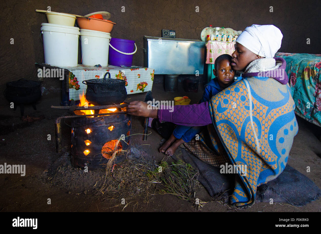 A child curiously looks on as his mother cooks a meal over a small fire pit in a rural Basotho home. - Stock Image