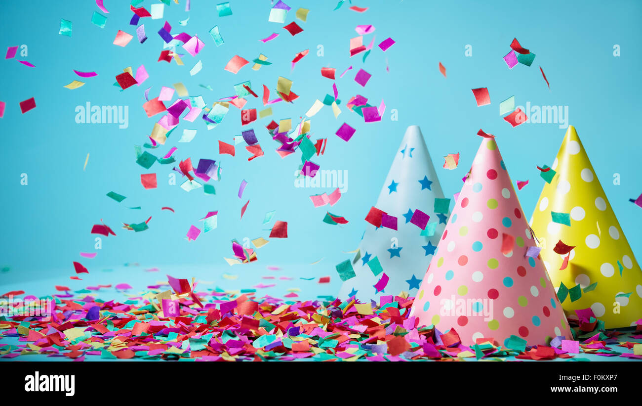 Colored confetti and party hat on blue background - Stock Image