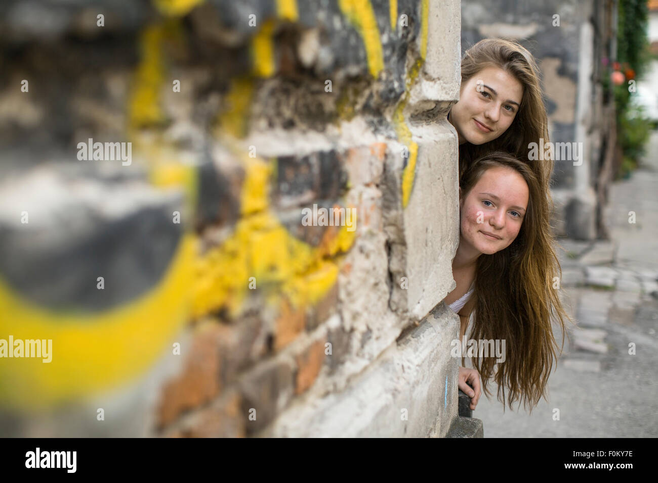 Two teenage girls look out behind the corner of the house. - Stock Image