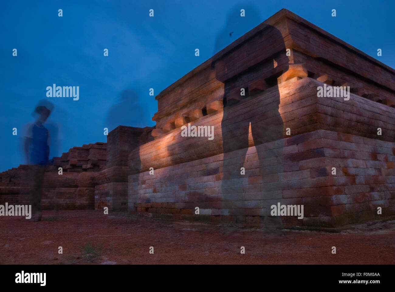 People illuminating ancient temple. - Stock Image