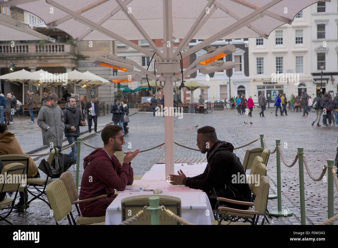 Two men at an outdoor table in Covent Garden, London - Stock Image