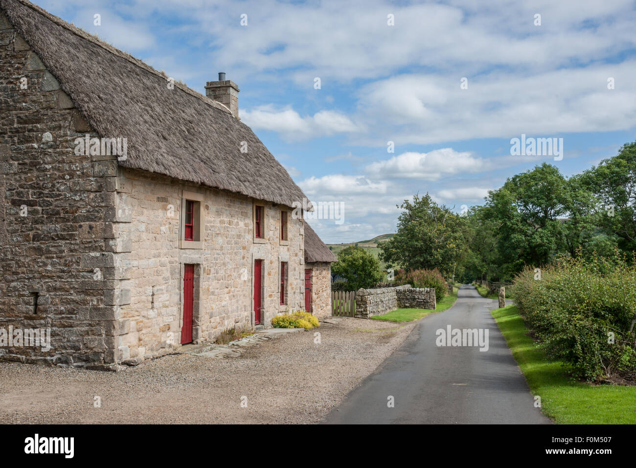 a quaint English stone cottage with a thatch roof - Stock Image
