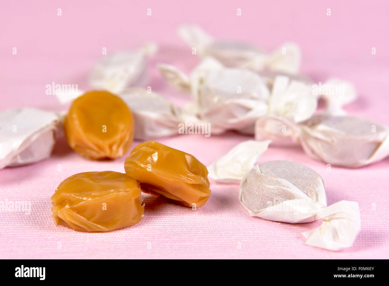 Toffees on pink background, some open and some in wrappers - Stock Image