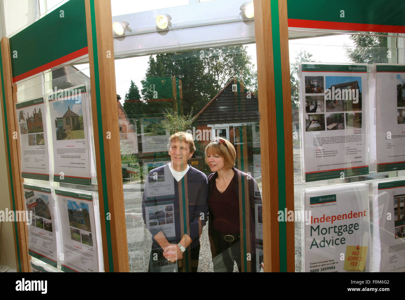 middle aged couple looking in estate agents window - Stock Image