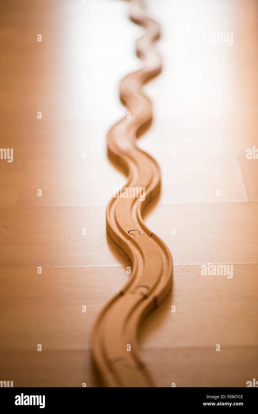 Wooden toy train track on floor. The tracks is winding forward into the light. Stock Photo