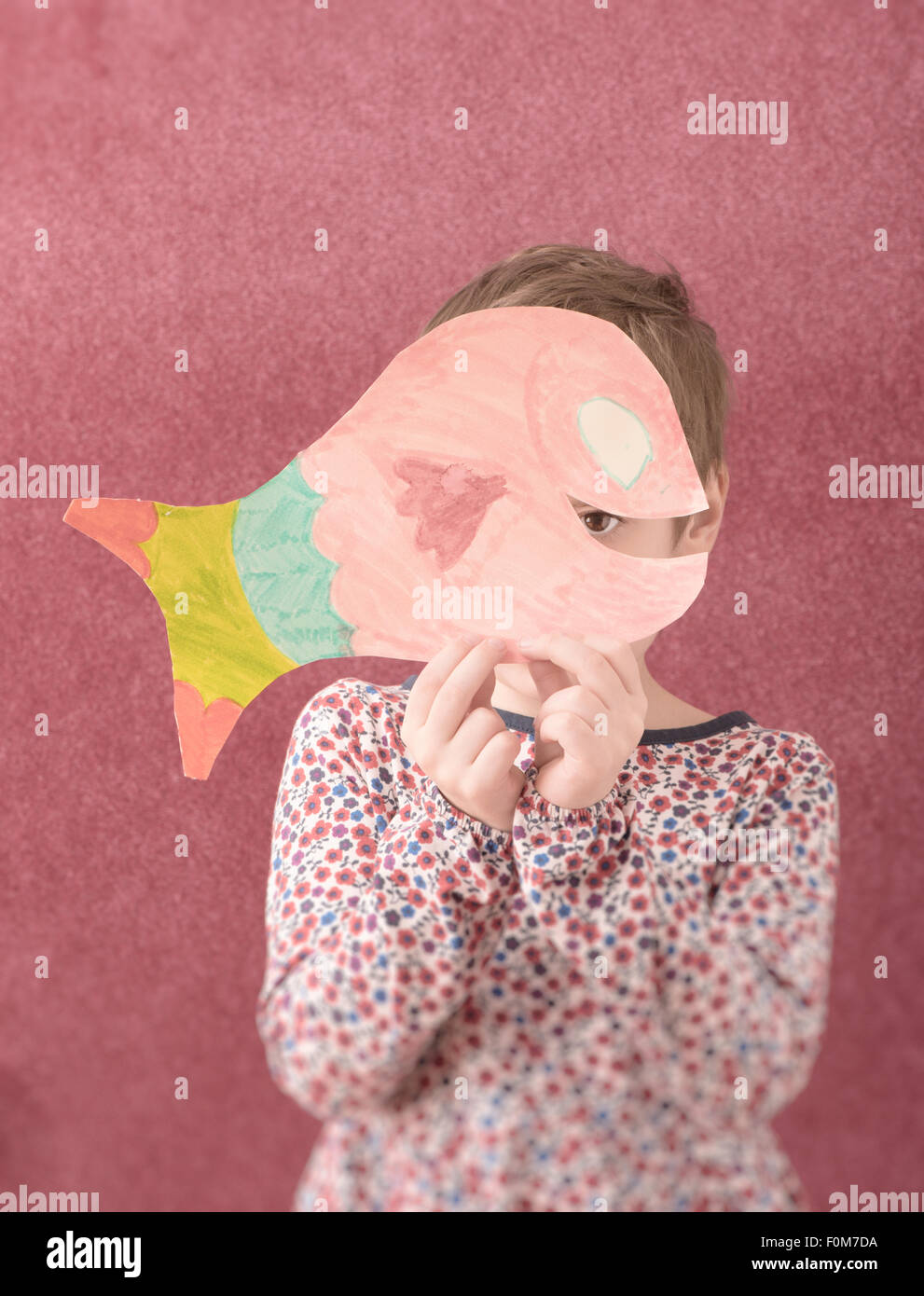 Portrait of little girl in dress holding a cut out drawing of a fish in front of her face. She is shy and hiding - Stock Image