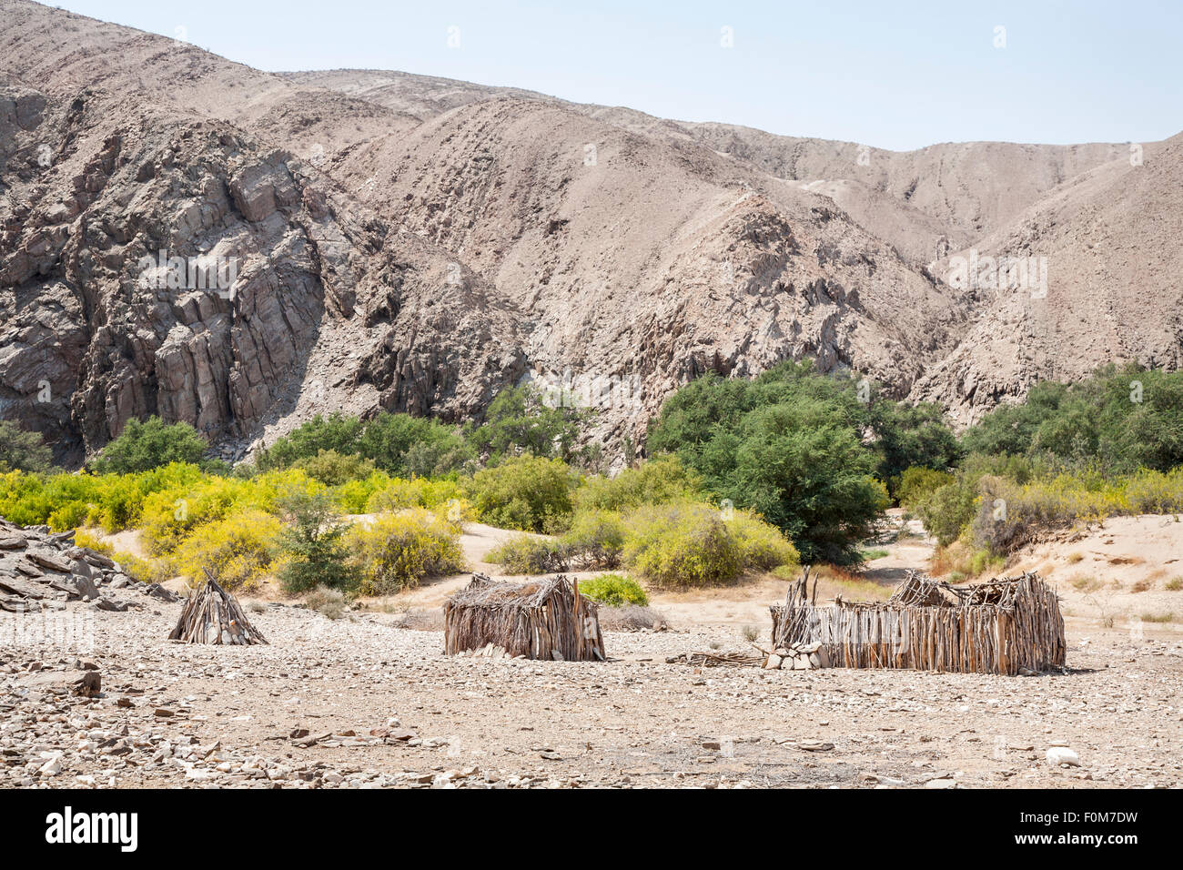 Angolan lifestyle and landscape: abandoned timber framed mud huts in rugged, arid desert terrain, southern Angola - Stock Image