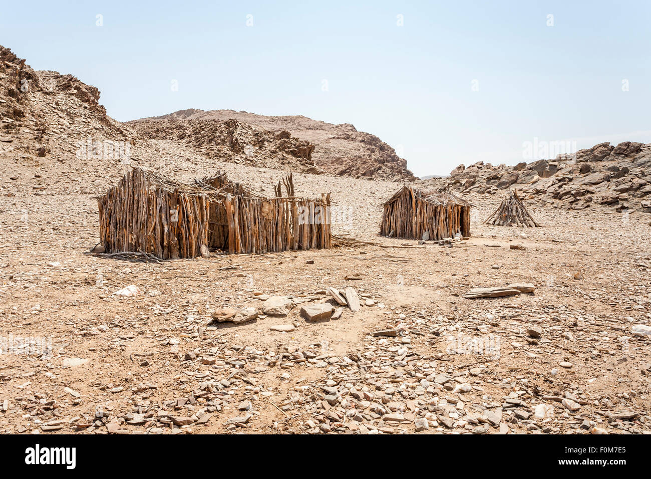 Angolan landscape and lifestyle: abandoned wooden frames of primitive mud huts in arid desert terrain, southern - Stock Image