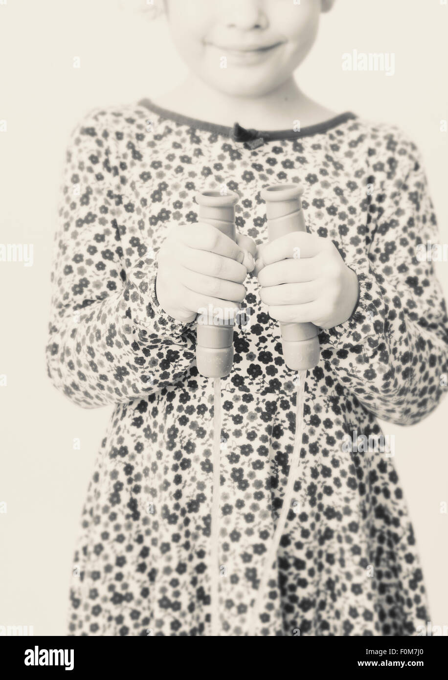 Portrait of little girl in dress with flowers. She is smiling and holding the handles of a jump rope. - Stock Image