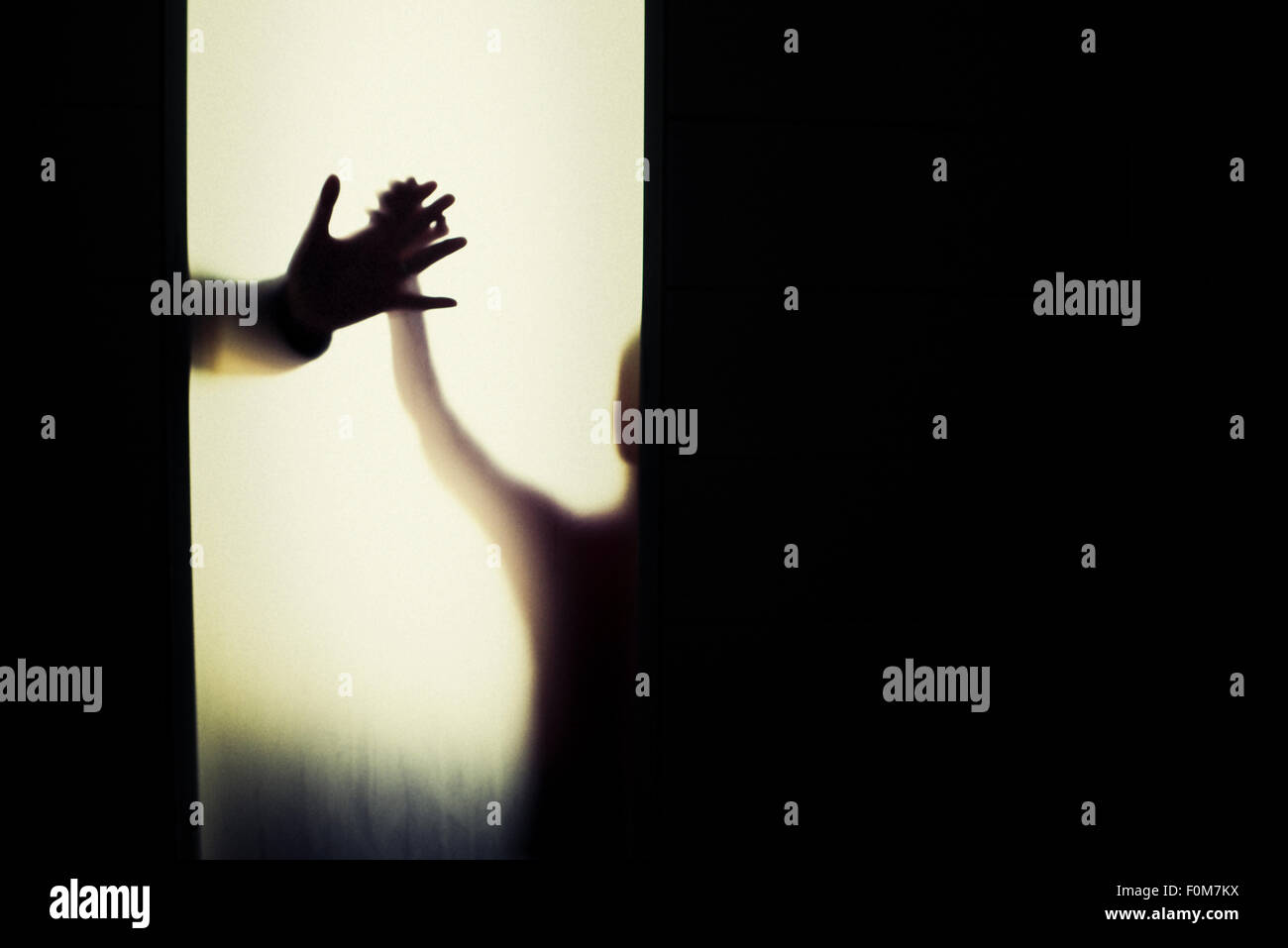Silhouette of child and adult holding hands. Conceptual image of trust, connection and bonding. Stock Photo