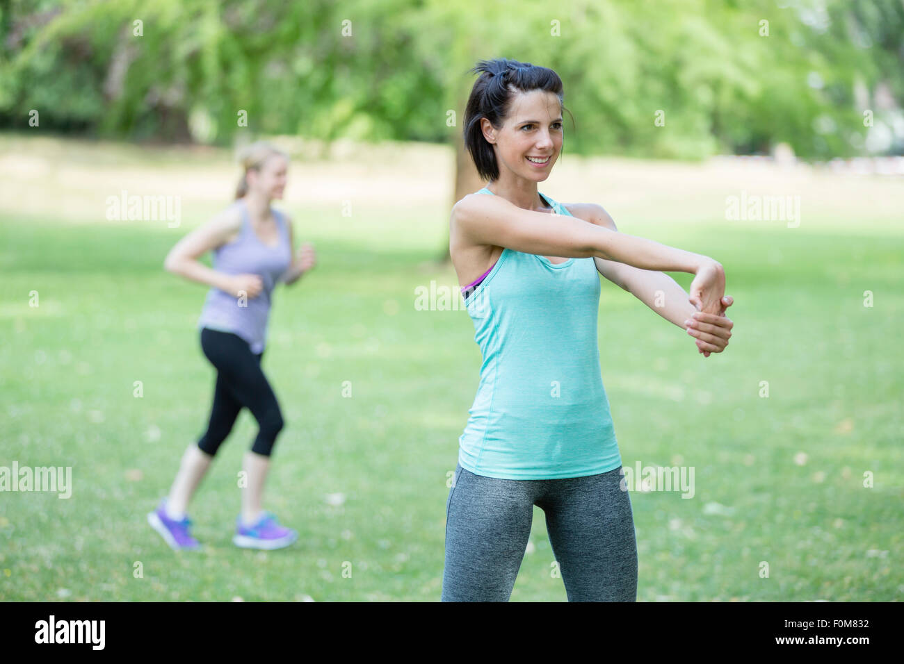 Two women stretch, warm up - Stock Image