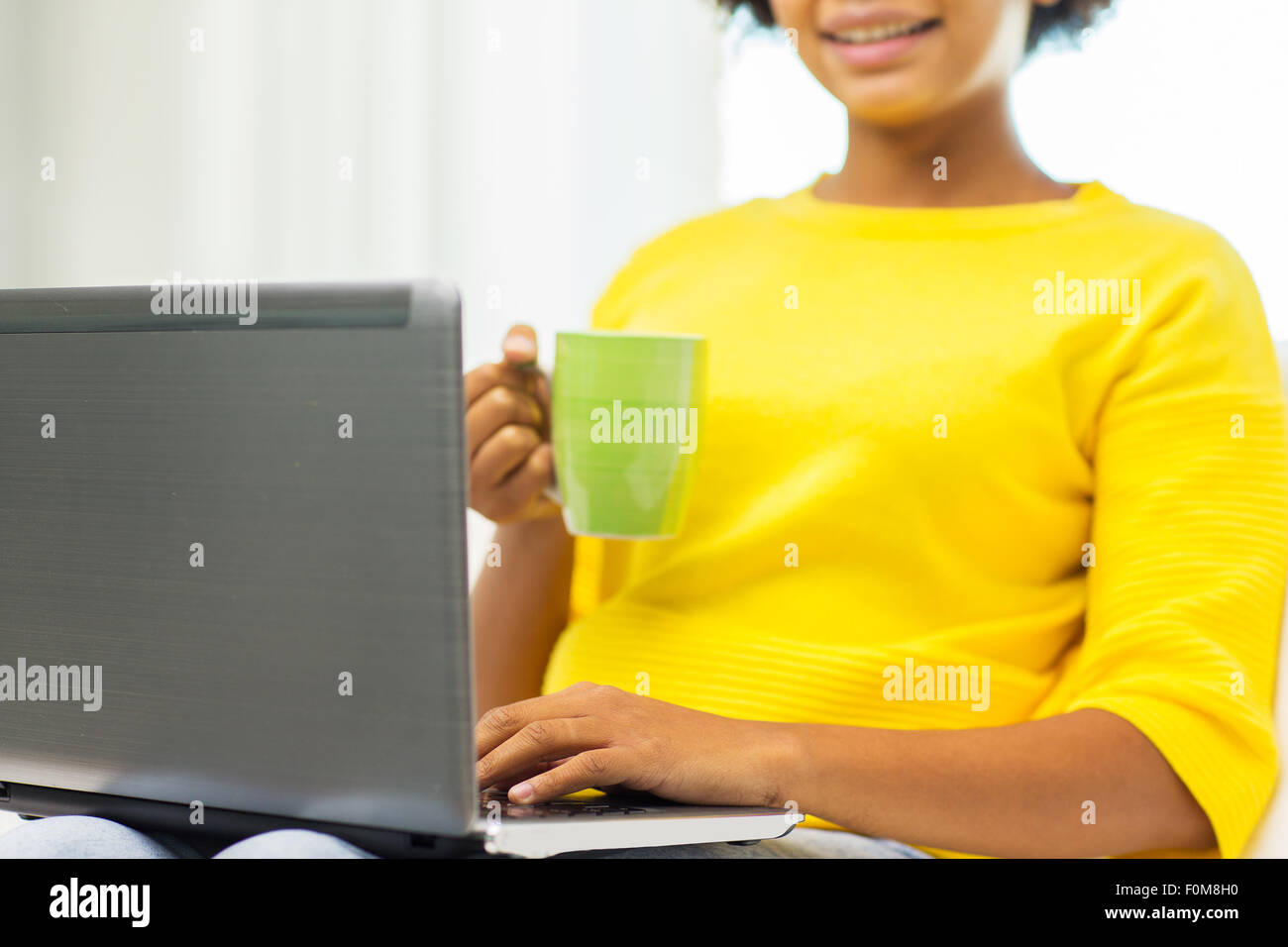 happy african american woman with laptop at home - Stock Image