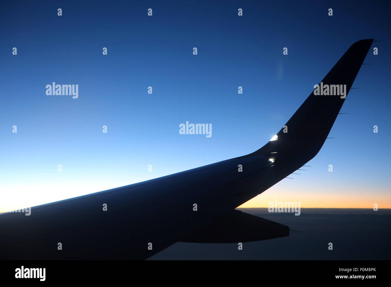 silhouette of airplane wing at dusk - Stock Image