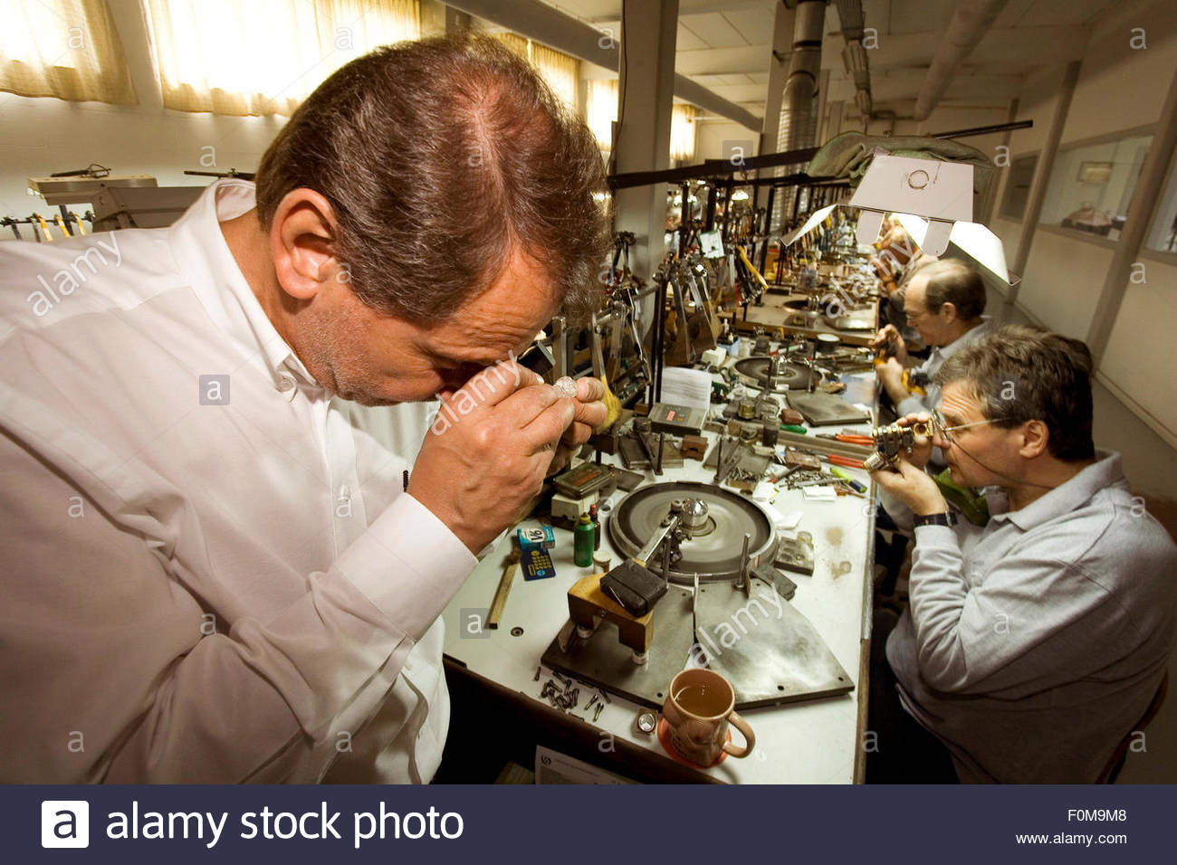 The production manager examins a diamond while the workers are cutting, polishing the diamonds, Overseas Diamonds - Stock Image